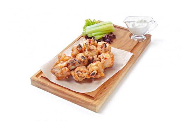 Knusprige grillhähnchenflügel mit sellerie auf hölzernem serviertablett