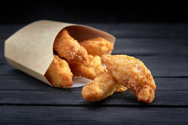 Knusprige hähnchenstreifen in papierbox auf dunkler oberfläche. junk fast food konzept. selektiver fokus. kopieren sie platz für text
