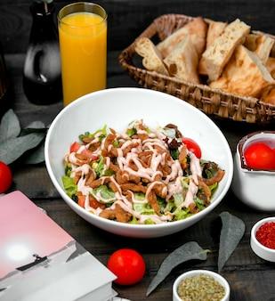 Knusprige hähnchenstreifen mit salat, tomate und mais, garniert mit mayonnaise