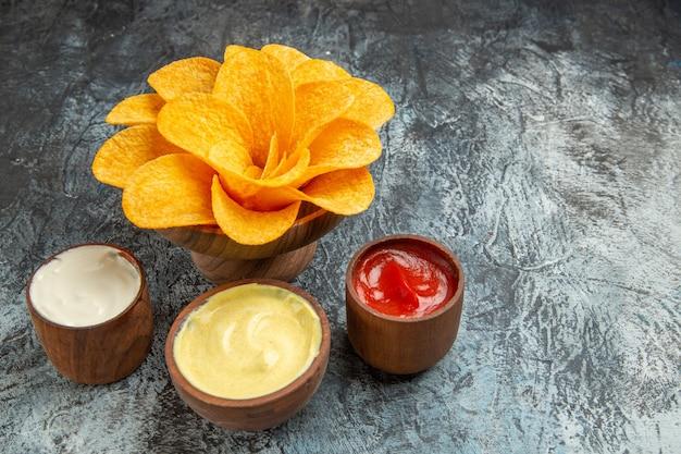 Knusprige kartoffelchips, dekoriert wie blütenförmiges salz, mayonnaise und ketchup auf grauem tisch