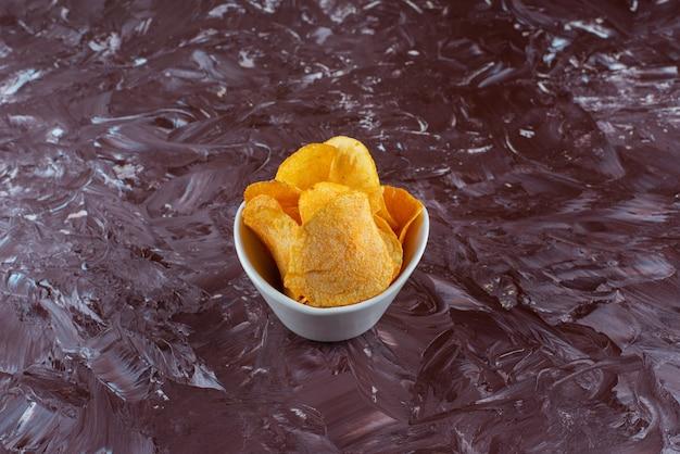 Knusprige kartoffelchips in einer schüssel auf dem marmortisch.
