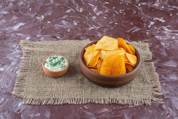 Knusprige kartoffelchips und joghurt in einem teller auf textur auf der marmoroberfläche
