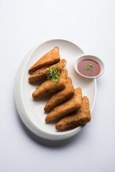Knusprige kartoffeldreiecke oder batata vada mit semmelbrösel bedeckt und dann frittiert. serviert mit tomatenketchup. selektiver fokus