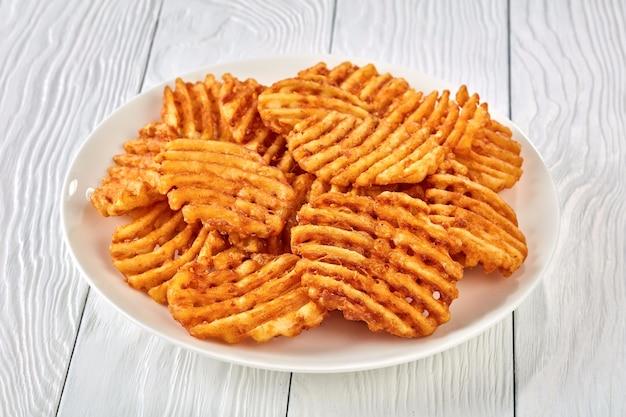 Knusprige kartoffelwaffel-pommes, gewellt, crinkle cut, criss cross fries auf einem weißen teller auf einem holztisch, ansicht von oben, nahaufnahme