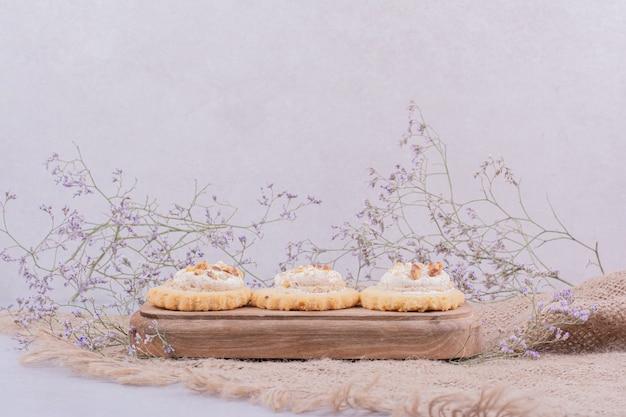 Knusprige kekse auf einem holzbrett auf einem stück sackleinen
