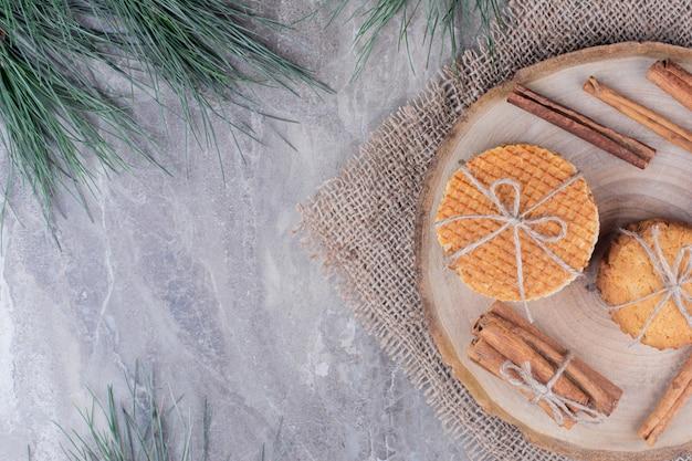 Knusprige kekse auf einem holzbrett mit zimtstangen herum