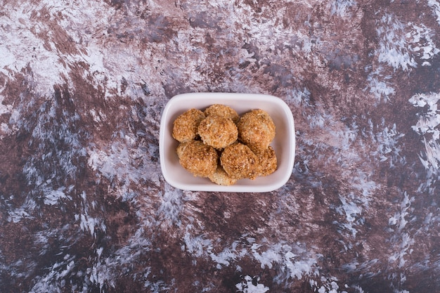 Knusprige kekse in einer weißen keramikuntertasse, draufsicht