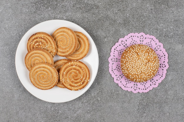 Knusprige kekse mit samen auf weißem teller mit frischem brötchen.