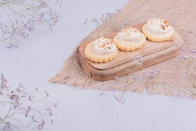 Knusprige kekse mit schlagsahne auf einem holzbrett