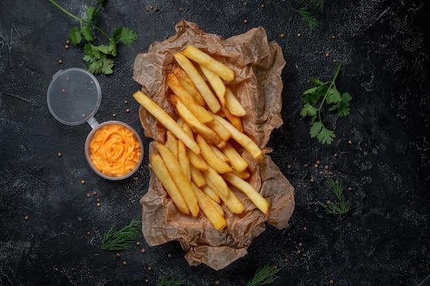 Knusprige leckere pommes frites auf dunklem steinhintergrund mit käsesauce. fastfood-restaurant. gesunde alternative zu fast food. bratkartoffeln