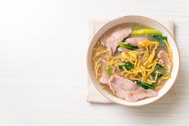 Knusprige nudeln mit schweinefleisch in soße. asiatischer essensstil