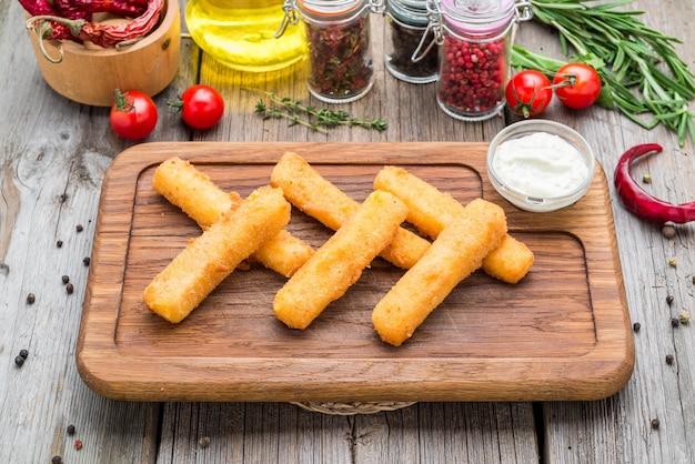 Knusprige panierte mozzarella-stangen mit senfsauce. schöne stilvolle speisekarte.