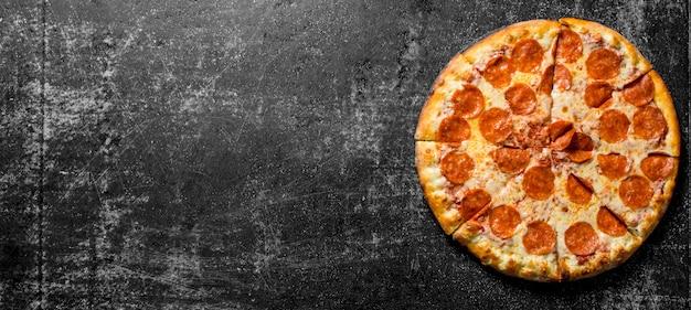 Knusprige peperoni-pizza mit würstchen und käse auf rustikalem tisch.