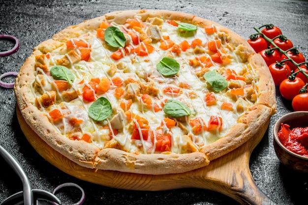 Knusprige pizza und kirschtomaten auf schwarzem rustikalem tisch.