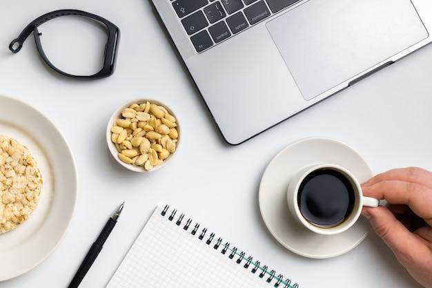 Knusprige reisrunden mit erdnüssen, tasse kaffee in der nähe des laptops, fitness-tracker und notizbuch.