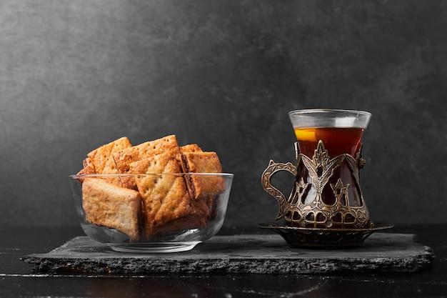 Knusprige risse in einer glasschale mit einem glas tee auf einem steinbrett.