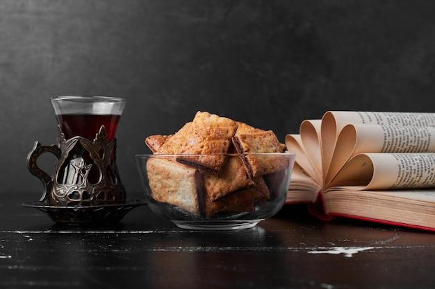 Knusprige risse in einer glasschale mit einem glas tee.