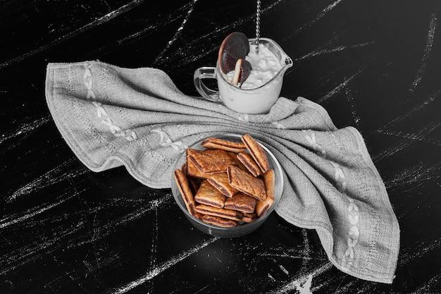 Knusprige risse in einer glasschale mit einer tasse eis beiseite.