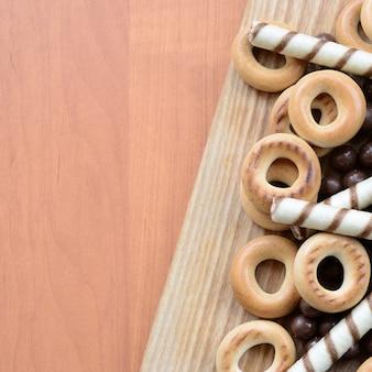 Knusprige röhrchen, schmelzende kugeln und bagels liegen auf einer holzoberfläche