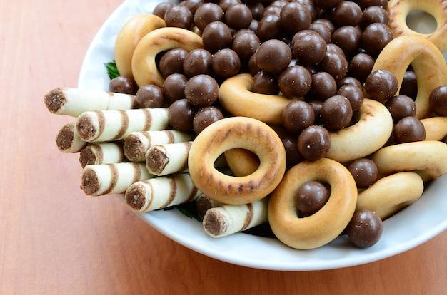 Knusprige röhrchen, schmelzende kugeln und bagels liegen in einer weißen platte auf einem holztisch