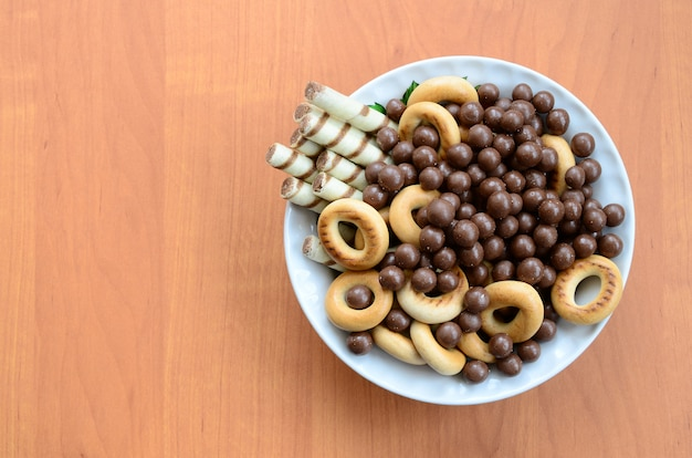 Knusprige röhrchen, schmelzende schokoladenbällchen und bagels liegen in einer weißen platte