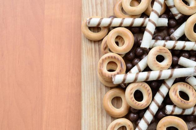 Knusprige röhrchen, schmelzende schokoladenbälle und bagel liegen auf einer holzoberfläche. mix aus verschiedenen süßigkeiten