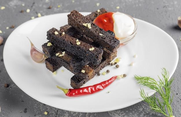 Knusprige roggencroutons oder snacks mit knoblauch und scharfem rotem pfeffer und sauce auf weißem teller