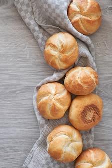 Knusprige runde brötchen, bekannt als kaiser- oder wiener brötchen, verteilt auf leinentuch auf rustikalem holz