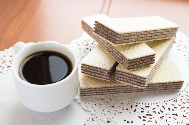 Knusprige schokoladenwaffeln auf weißer serviette und tasse kaffee.