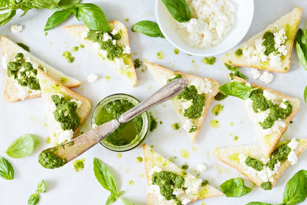 Knusprige toasts (crostini, bruschetta) mit hüttenkäse (ricotta) und frisch zubereitetem pesto. hausgemachte basilikum-pechto-sauce in einem glas an einer hellen wand.