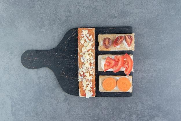 Knusprige toasts mit tomaten auf holzbrett.