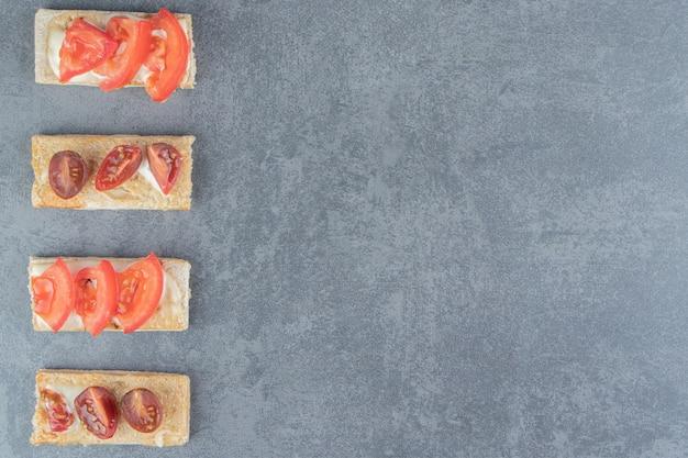 Knusprige toasts mit tomaten auf marmor.