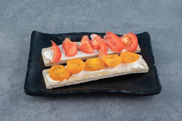 Knusprige toasts mit tomaten auf schwarzem teller.