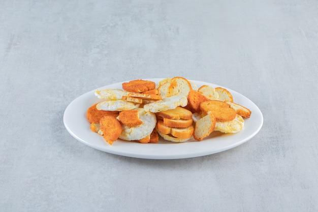 Knusprige vollkornreiskuchen und cracker auf weißem teller.