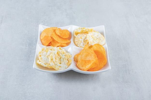 Knusprige vollkornreiskuchen und würzige chips in weißen schalen.