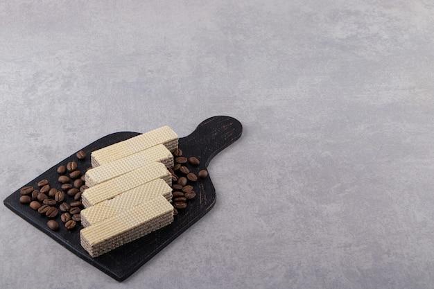 Knusprige waffeln mit kaffeebohnen auf steintisch.