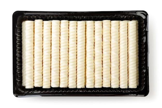 Knusprige waffelröhrchen mit füllung in der packungsnahaufnahme auf weißem hintergrund, isoliert. ansicht von oben