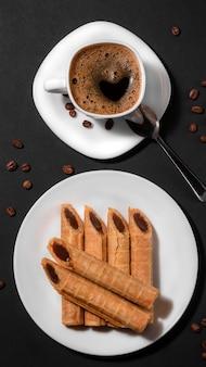 Knusprige waffelröllchen gefüllt mit gekochter kondensmilch und einer tasse kaffee