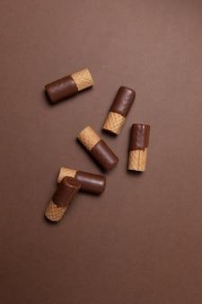 Knusprige waffelröllchen, halb mit milchschokolade überzogen Premium Fotos