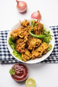 Knusprige zwiebelbhajis oder kanda pakoda oder pyaj ke pakore, köstliches indisches und brasilianisches streetfood auf salat, typischerweise in der regen- oder monsunzeit mit heißem tee genossen, selektiver fokus