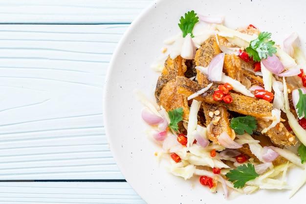 Knuspriger gouramifisch mit scharfem salat