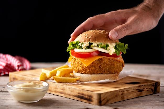Knuspriger hühnerburger mit käse und pommes frites auf holztisch