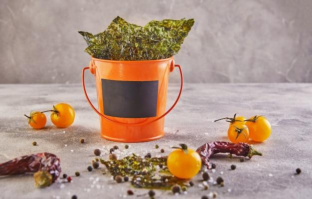 Knuspriger nori-seetang mit kirschtomaten und gewürzen in einem orangefarbenen eimer auf grauem beton. japanisches essen nori. getrocknete algenblätter. attrappe, lehrmodell, simulation