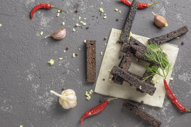 Knuspriger roggentoast oder snacks mit knoblauch und heißem rotem pfeffer auf grauem betontisch
