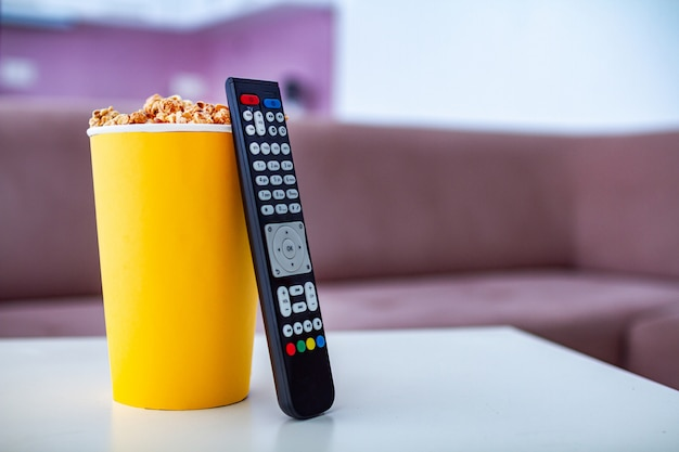Knuspriger süßer karamellpopcornkasten für snack während zu hause fernsehen. popcorn-film.