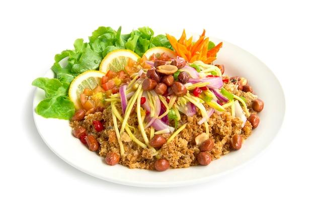 Knuspriger wels des würzigen salats mit heißem leckerem essen der mangoscheibe heißes thailändisches auf oben gebratenen erdnüssen verzieren mit grünem eichenchili geschnitzt und zitronenseitenansicht lokalisiert auf weißem hintergrund