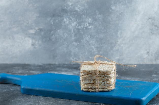 Knuspriges brot im seil auf einem hölzernen schneidebrett.