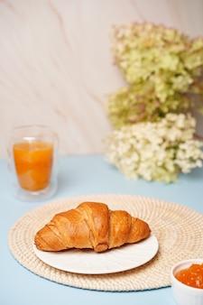 Knuspriges croissant auf blauem hintergrund mit marmelade und orangensaft, leckeres frühstück. foto in hoher qualität