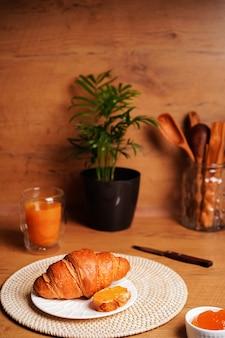 Knuspriges croissant auf einem teller auf einem holztisch neben marmelade und orangensaft, leckeres frühstück. foto in hoher qualität