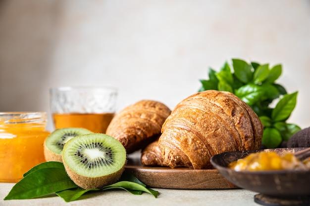 Knuspriges croissant mit orangenmarmeladesaft und kiwi leckeres frühstück